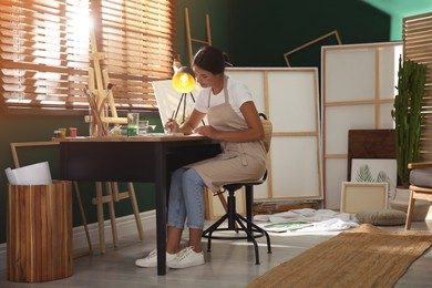 Young woman drawing with watercolors at table indoors