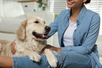 Young woman and her Golden Retriever at home, closeup. Adorable pet