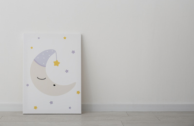 Adorable picture of moon and stars on floor near white wall, space for text. Children's room interior element