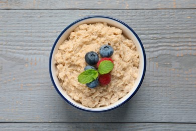 Tasty oatmeal porridge with berries on grey wooden table, top view