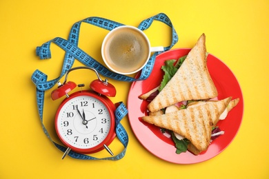 Flat lay composition with tasty sandwiches and alarm clock on yellow background. Nutrition regime