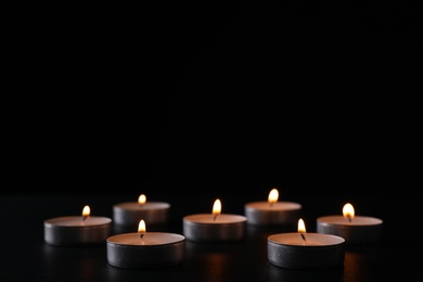 Burning candles on black background, space for text. Holocaust memory day