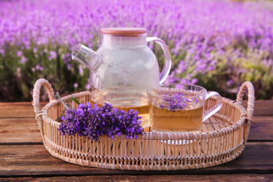 Tasty herbal tea and fresh lavender flowers in tray on wooden table outdoors, closeup