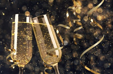 Glasses with sparkling wine and shiny serpentine streamers against blurred festive lights