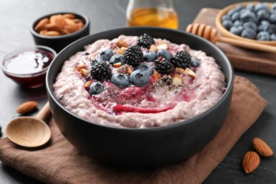 Tasty oatmeal porridge with toppings in bowl served on table, closeup