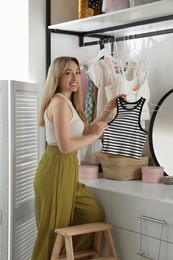 Woman with top near rack indoors. Interior design