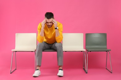 Man waiting for job interview on pink background