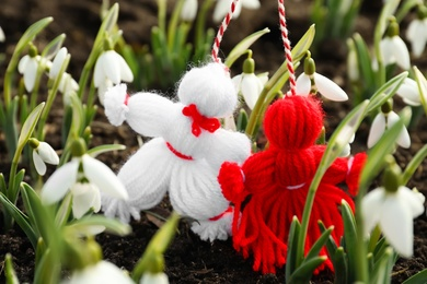 Traditional martisor among beautiful snowdrops outdoors. Beginning of spring celebration