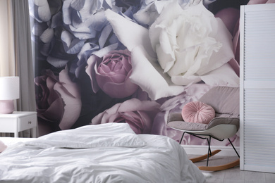 Comfortable bed near wall with floral wallpaper. Stylish room interior