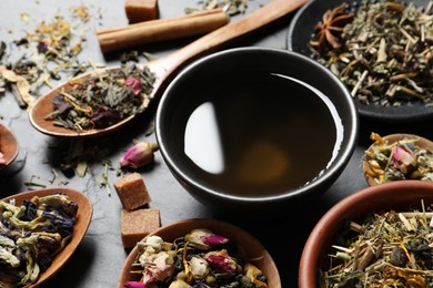 Fresh brewed tea and dry leaves on grey table, closeup