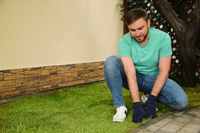 Young man laying grass sod at backyard, space for text