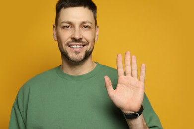 Left-handed man with open palm on yellow background