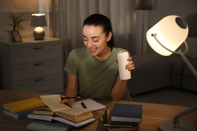 Young woman with energy drink studying at home