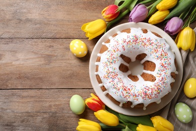 Glazed Easter cake with sprinkles, painted eggs and tulips on wooden table, flat lay. Space for text