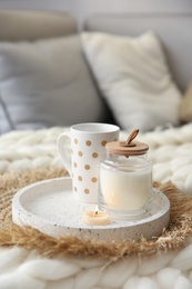 Cup of drink and candles on knitted plaid in room. Interior elements