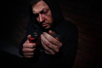 Man preparing drug with spoon and lighter near brick wall