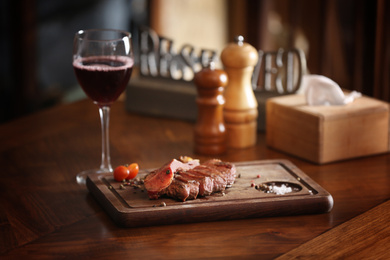 Tasty roasted meat served on wooden table in restaurant. Cooking food