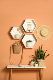 Shelves and table with decorative elements on color wall. Interior design