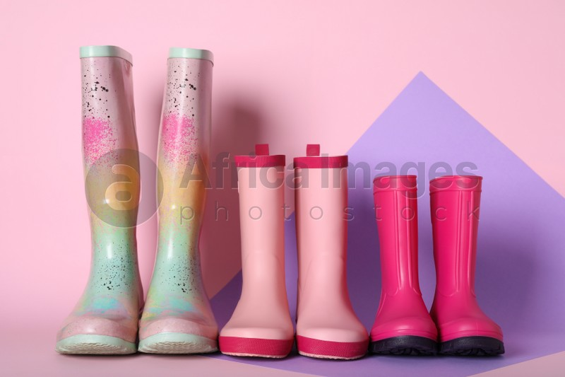 Three pairs of rubber boots on color background