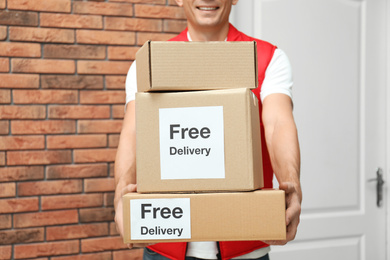Courier holding parcels with stickers Free Delivery indoors, closeup