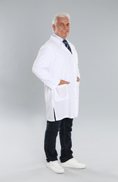 Happy senior man in lab coat on light grey background