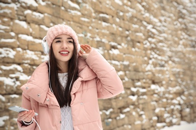 Young woman listening to music with headphones near stone wall. Space for text