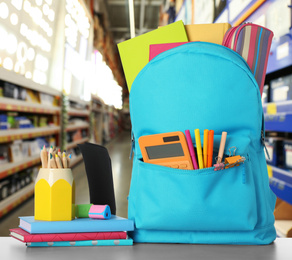Bright backpack with school stationery on table in shopping mall