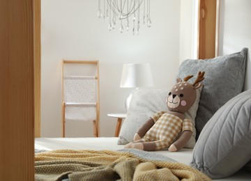Comfortable wooden house bed with cushions and toy in child room. Interior design