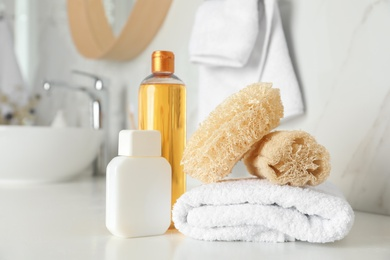 Natural loofah sponges, towel and cosmetic products on table in bathroom