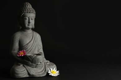 Beautiful stone Buddha sculpture with flowers on black background. Space for text