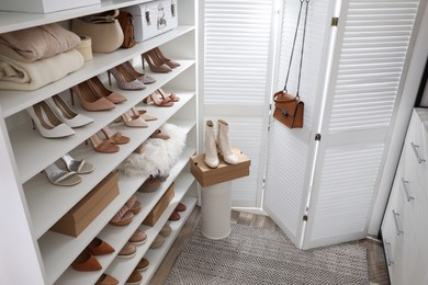 Dressing room interior with stylish shoes and accessories on shelves, above view