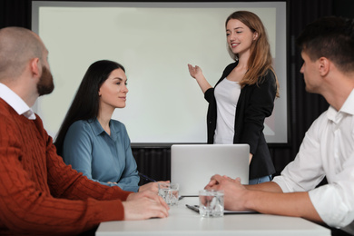 Business people having meeting in conference room with video projection screen