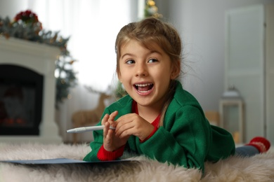 Cute child writing letter to Santa Claus at home. Christmas tradition