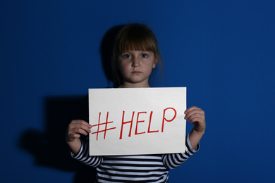 Abused little girl with hashtag HELP near blue wall. Domestic violence concept
