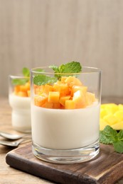 Delicious panna cotta with mango on wooden table