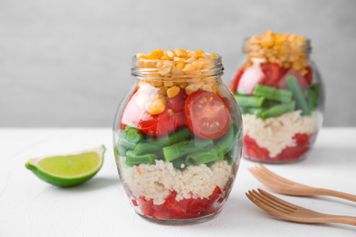Healthy salad in glass jars on white table