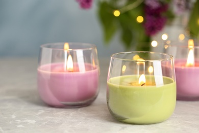 Burning candles in glass holders on grey table against blurred lights