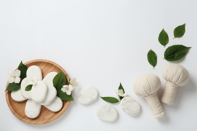 Spa stones, beautiful jasmine flowers and herbal bags on white background, flat lay. Space for text