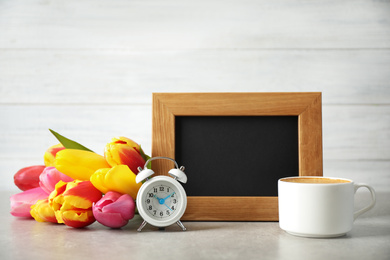 Chalkboard with morning wish, delicious coffee, tulips and alarm clock on light grey table