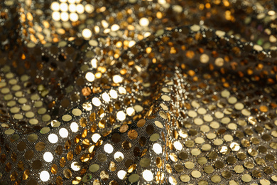 Texture of beautiful golden fabric with paillettes as background, closeup