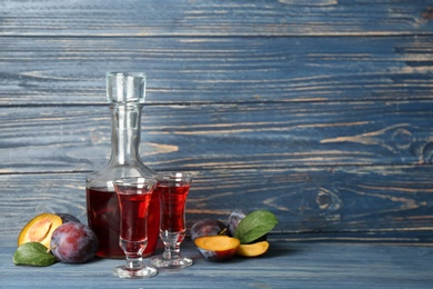 Delicious plum liquor and ripe fruits on blue wooden table. Homemade strong alcoholic beverage