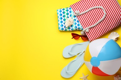 Flat lay composition with ball and beach objects on yellow background, space for text