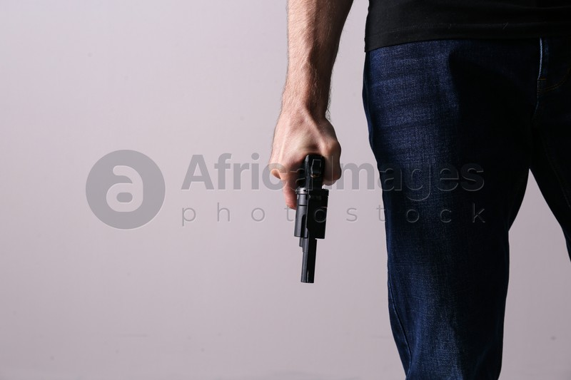 Man holding gun on grey background, closeup. Space for text