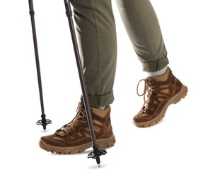 Woman wearing stylish hiking boots with trekking poles on white background, closeup
