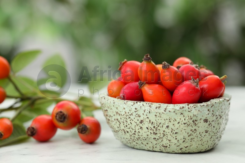 Ripe rose hip berries with green leaves on white wooden table outdoors, closeup. Space for text