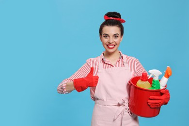 Young housewife holding bucket with cleaning supplies on light blue background, space for text