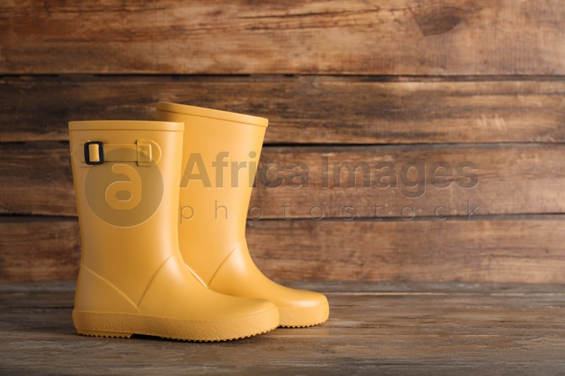 Pair of yellow rubber boots on wooden surface. Space for text