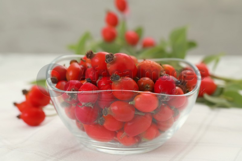 Ripe rose hip berries in bowl on white table, closeup
