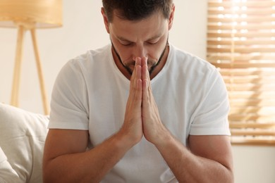 Religious man with clasped hands praying indoors