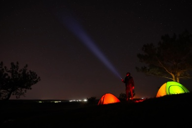 Man with bright flashlight near camping tents outdoors at night